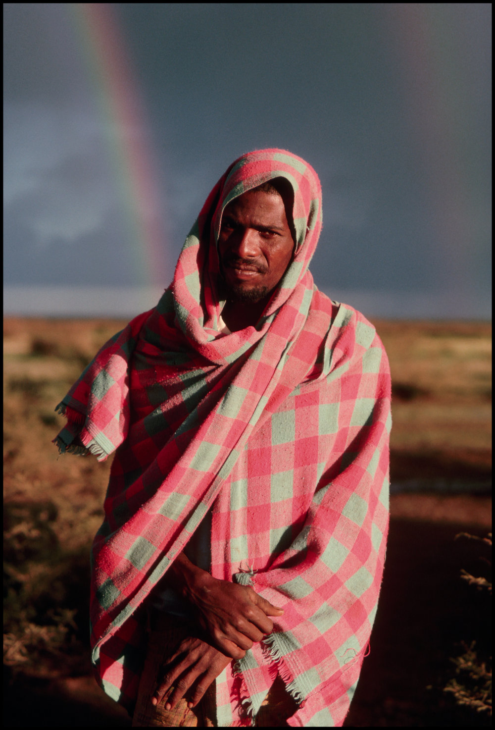 1988, Somalia --- Refugee Posing in Front of Rainbow