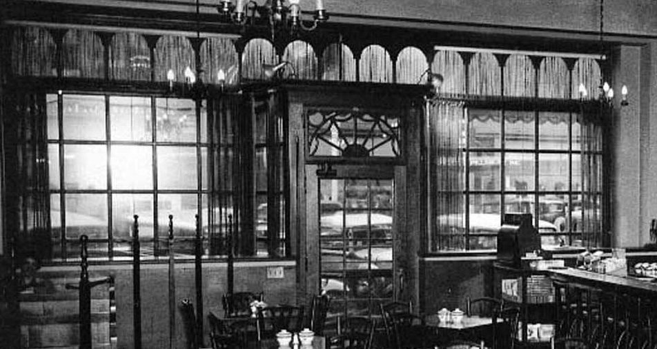 A 1933   interior photo of the Hotel Windham Coffee Shop Facade. This facade was changed after the building was purchased in 1944 and included an automatic door opener. Then, after 1966, the facade was 'Remuddled'. See below.