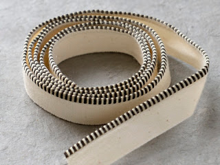 Faux endbands can be purchased by the foot or yard. C  ut to the width of the book spine and glue   on, with the glue being applied only to the   linen or cotton tape portion of the end  band—  the light colored fabric portion seen in the above image is either   linen or cotton tape which the faux endband is sewn onto  .