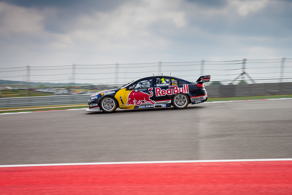 Points leader Jamie Whincup in the Red Bull Racing Australia #1 car puts the hammer down out of turn 1 at Circuit of the Americas Race Track in Austin, Texas.