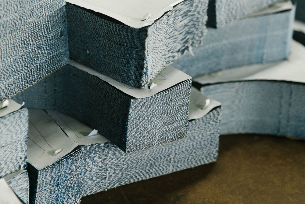 Stacks of individual panels, cut precisely according to the master pattern, wait to be assembled into pairs of jeans. (Photo: Angi Welsch/Surface)