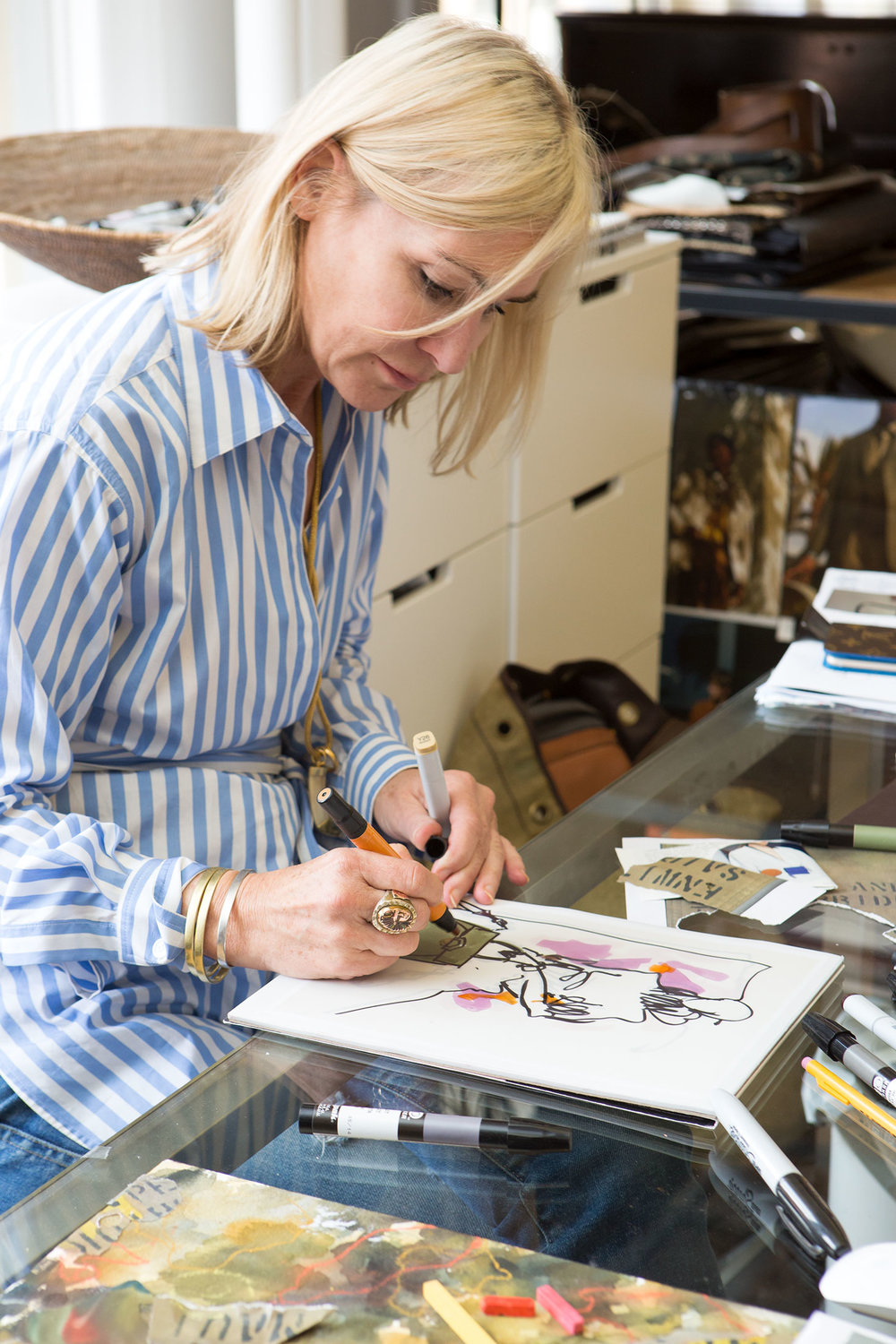 Formby sketching at her desk.