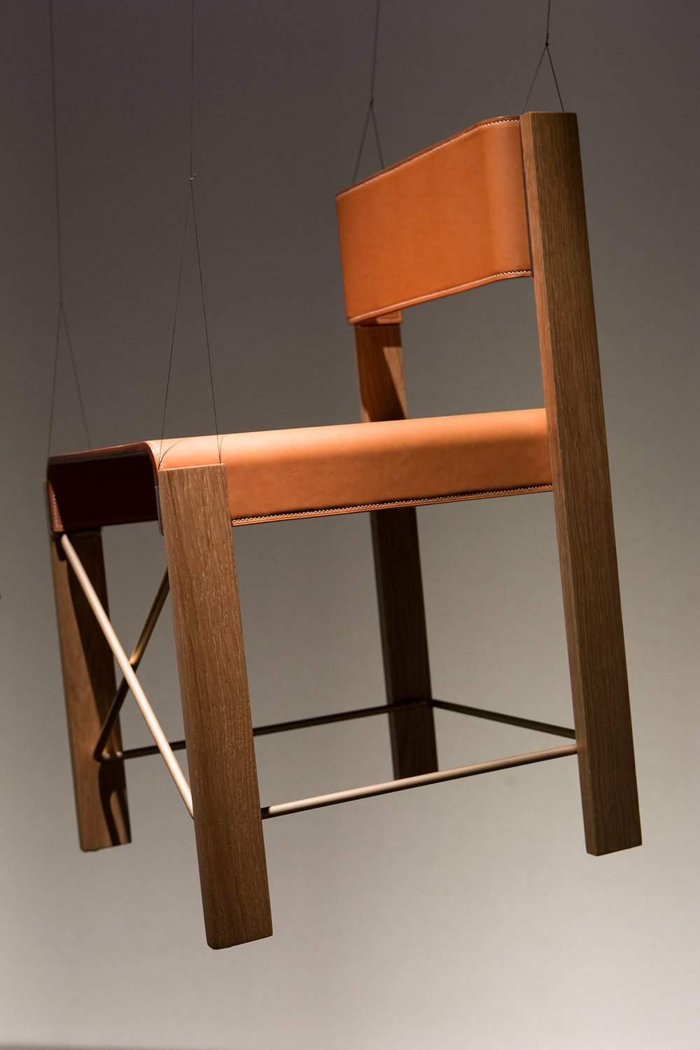 The Equis chair in calfskin, oak, and brushed brass.