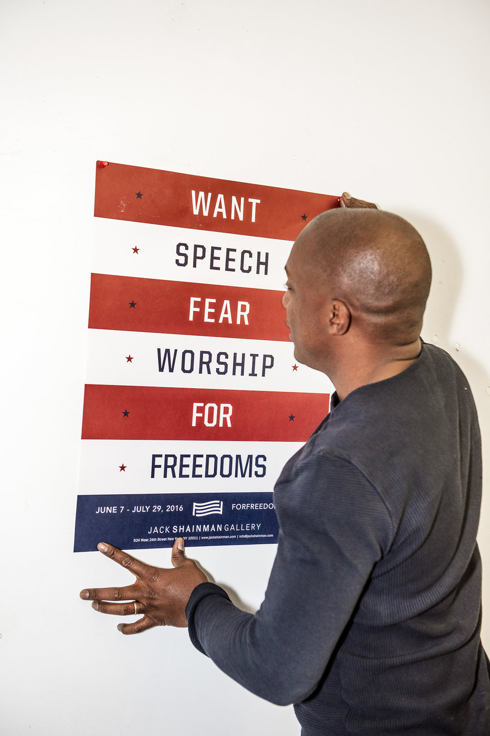 "Thomas with a poster advertising ""For Freedoms,"" an exhibition at Jack Shainman Gallery that showcased commissions made for the super PAC."