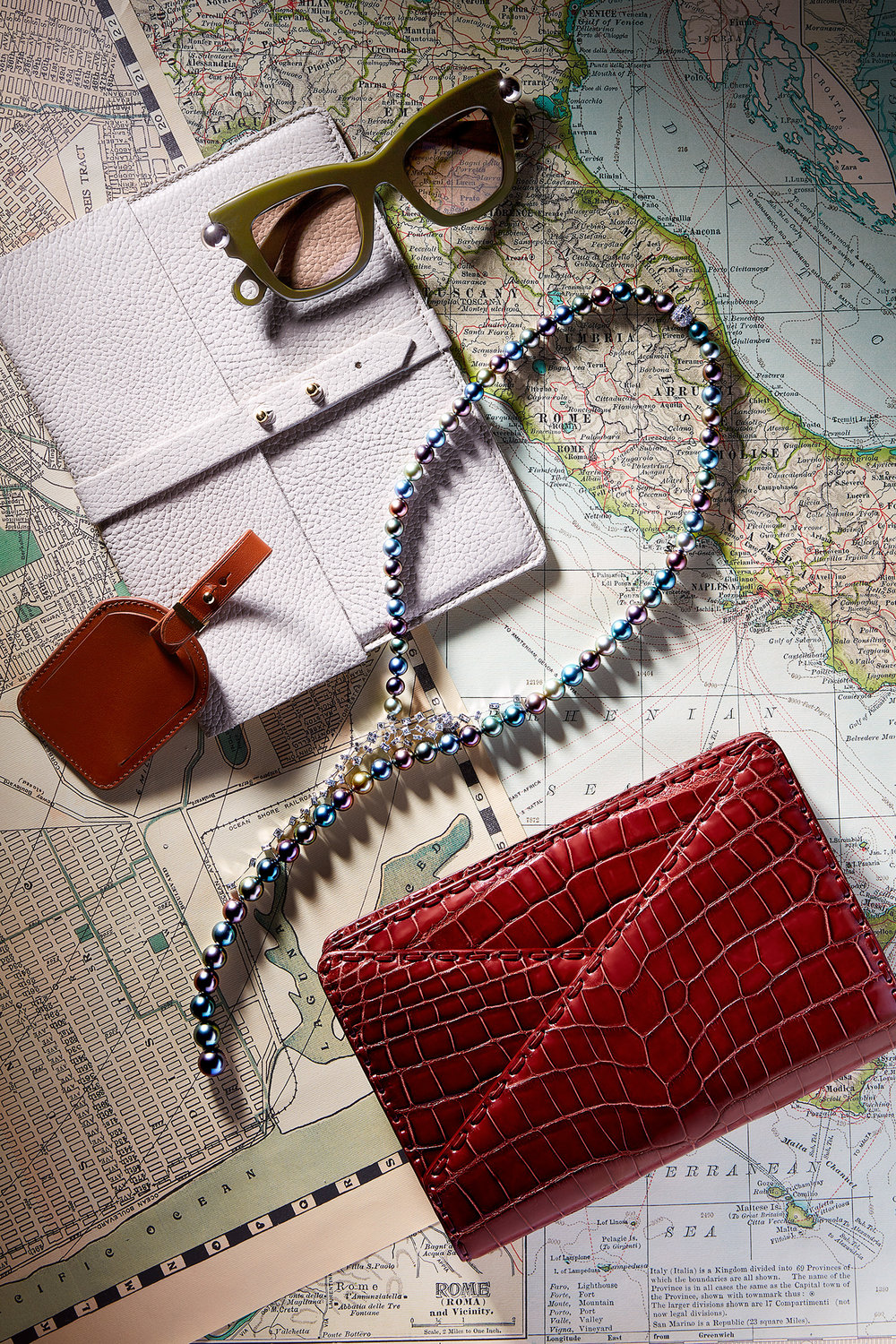 (FROM TOP) Pouch and luggage tag,  Cuyana . Sunglasses,  Christopher Kane . Necklace,  Mikimoto . Clutch,  Bottega Veneta .