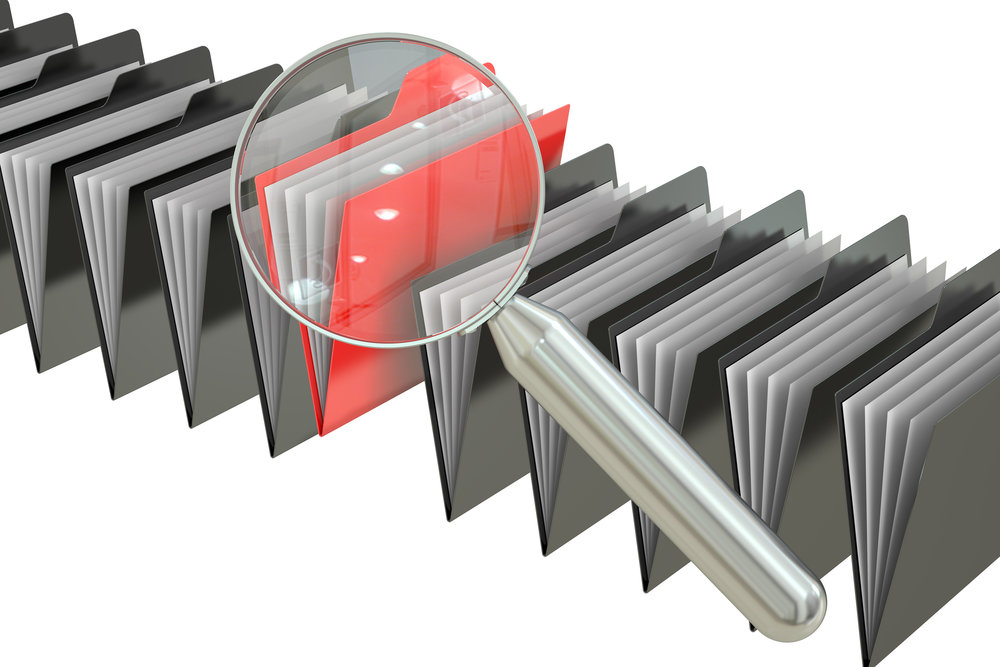 Magnifying glass over red file folder.jpg