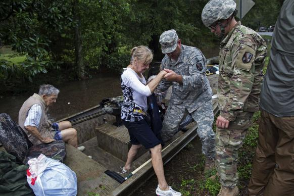 Photo by Max Becherer, Associated Press Members of the Louisiana Army National Guard rescue people from rising floodwater near Walker, La., after heavy rains inundated the region, Sunday, Aug. 14, 2016. .