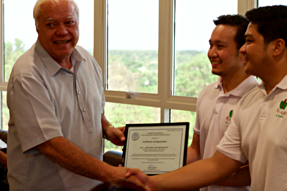 Ala Amid Bed & Breakfast receiving a certificate of recognition from Puerto Princesa City Mayor Lucilo Bayron