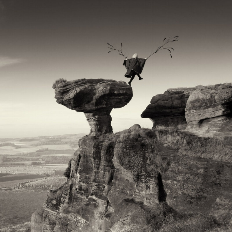 photograph by Laurence Winram of a woman leaping from Bonnet Rock in Fife
