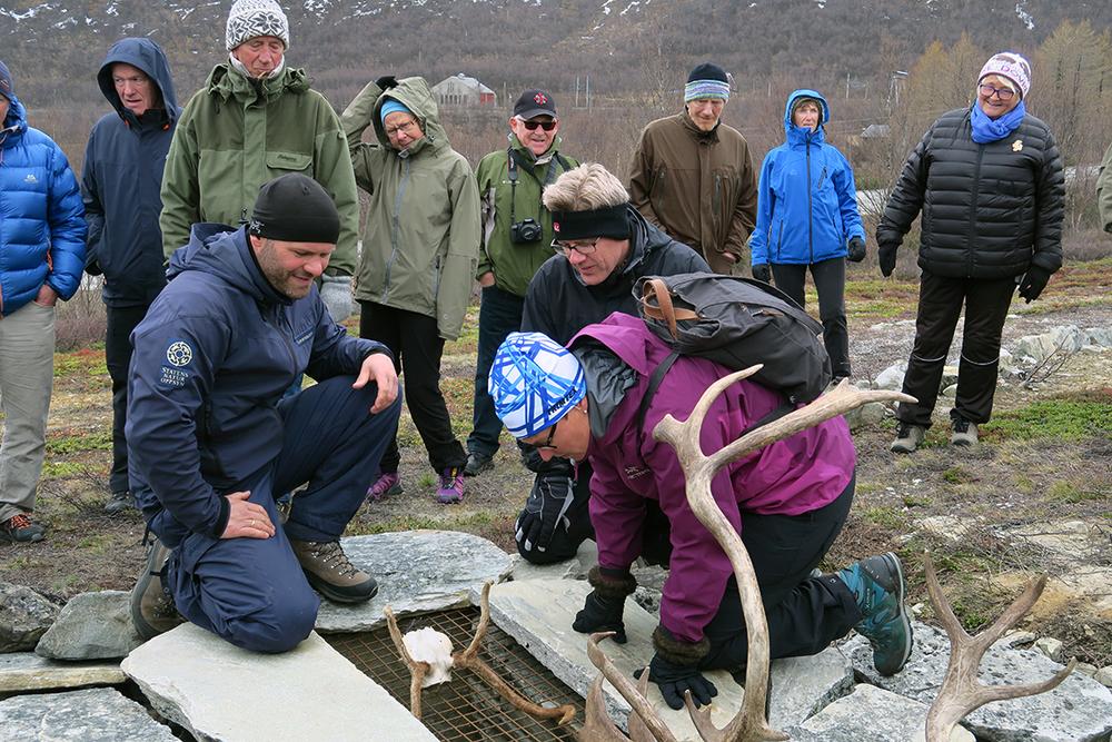 Klima- og miljøminister Tine Sundtoft sjekker en av de rekonstruerte fangstgropene for villrein. Dyktig informant er SNOs Espen Rusten (til venstre). Foto: A. Nyaas