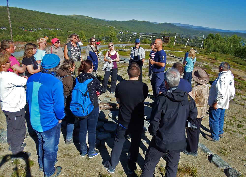 Naturveileder Espen Rusten ved Norsk Villreinsenter Nord på Hjerkinn forteller med stor innlevelse om gamle fangstgraver. Foto: Tor Punsvik