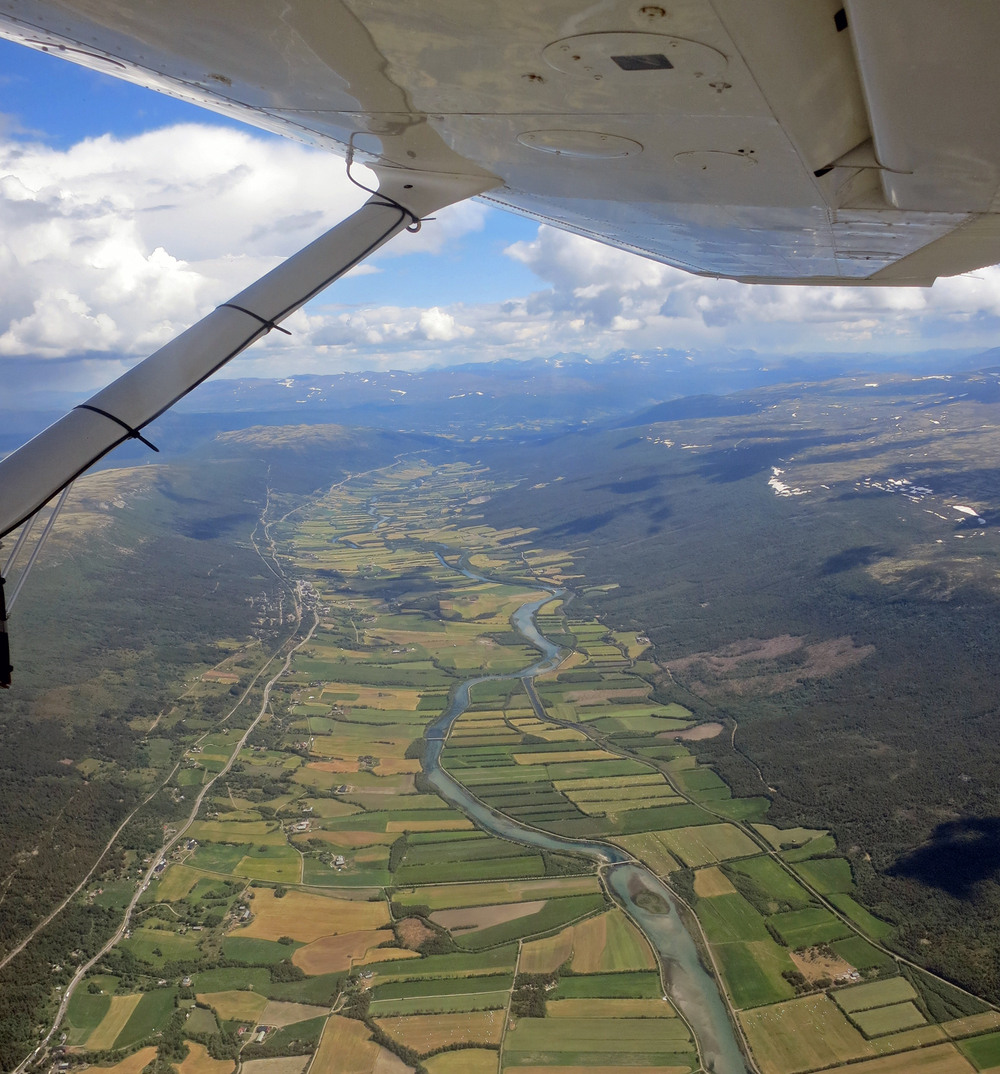 Reinheimen-Breheimen 2. juli 2014: Her flyr vi over jordbruksbygda Lesja. Foto: A. Nyaas