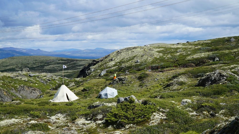 Arkeologenes leir ved siden av de utgravde hustuftene som kan ses til venstre i bildet.