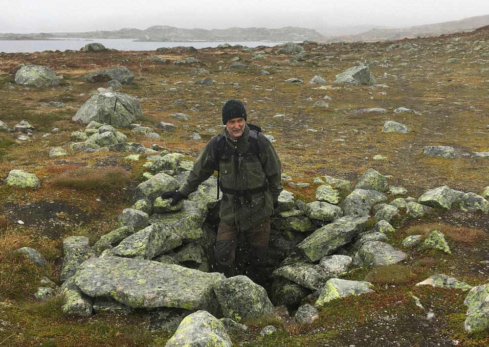 Torstein Seim, ivrig lokalhistorikar frå Hol, her i ei dyregrav ved Drageidfjorden, ikkje langt frå Krækkja turisthytte.