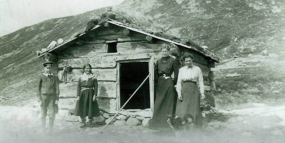 Ved den vesle bua i Sandvasskvæven i Rysstadheia der sørsamane Lars og Sigrid Johnsen heldt til sommarstid i perioden 1907 og 1915. Alle personane bortsett frå éin, er ukjente, nr. to frå vestre er Brita Bergli, mor til Sigrid, ho budde òg i denne bua (foto utlånt av Lajla Renander).