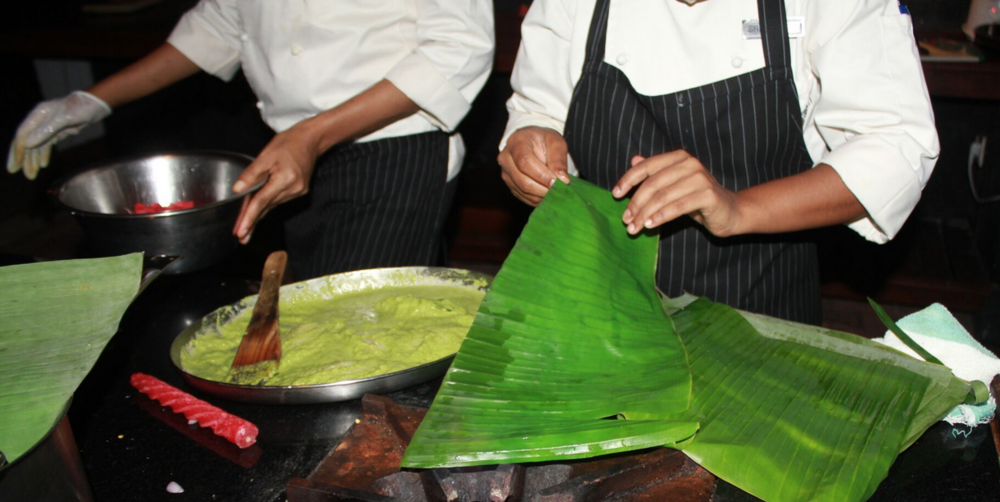Warming banana leaves to make them flame retardant; making marinaded fish parcels in our cooking class, Marikulam