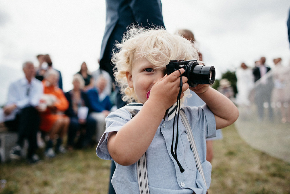 Kid helping out with the photography at a wedding