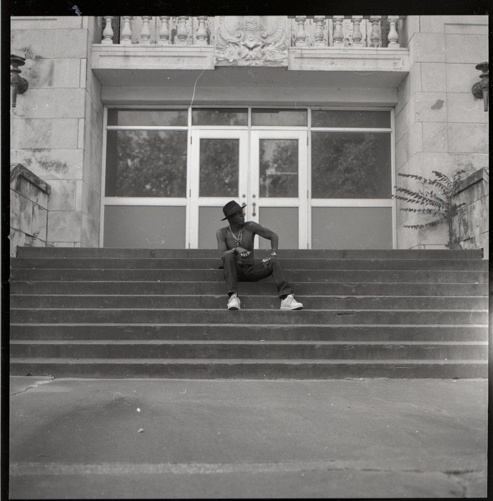 Dewayne sitting on the steps of his old, now vacated, middle school.