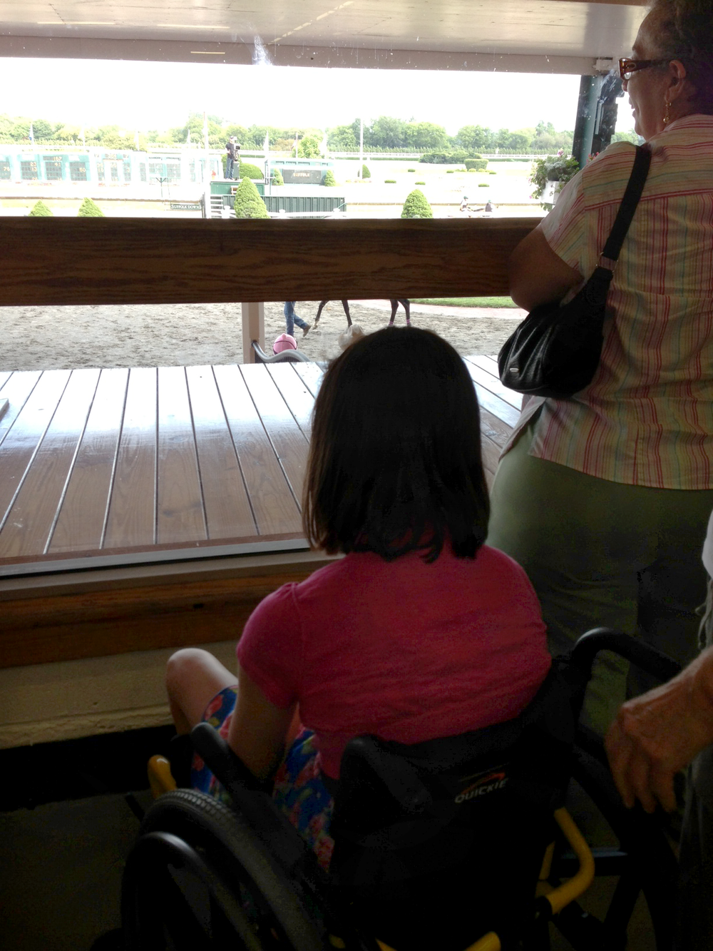 The jockey looked at the girl sitting on the rail and waved again as the entire family waved back and wished her luck.