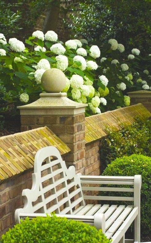 Garden hydrangaeas white left boxwood luytens bench brick wall.jpeg