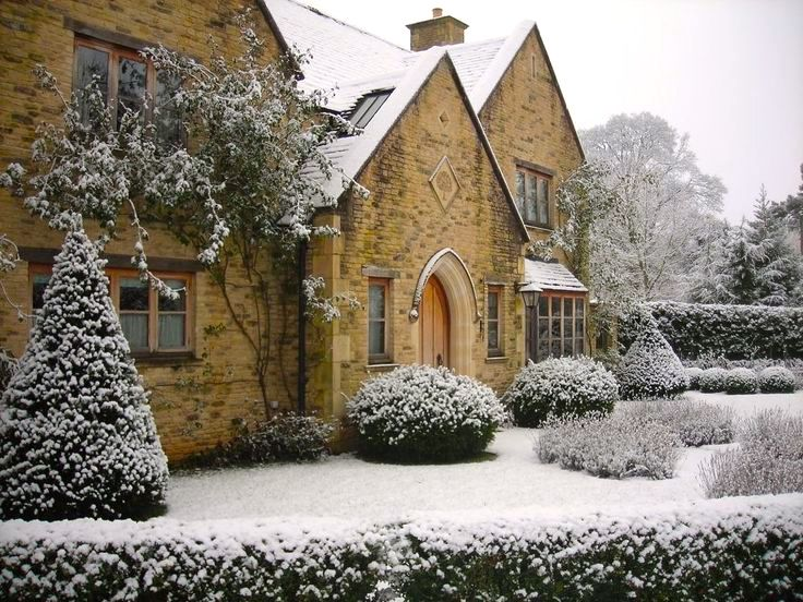 Topiary winter stone home facade winter snow covered.jpg