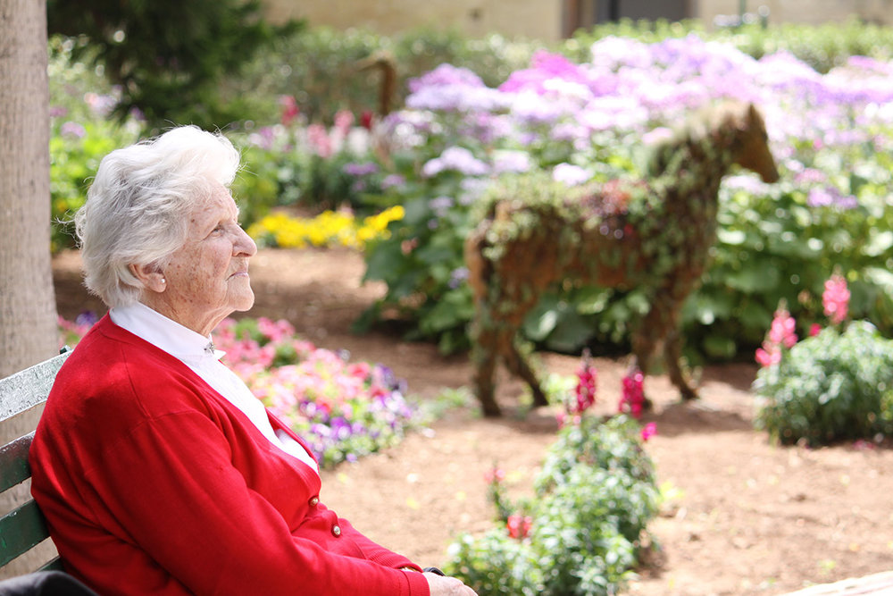 Healthcare_Garden_Design_woman_enjoying_garden_memory-unit.jpg