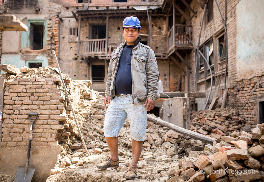 A man pauses whilst rebuilding his sister's house, which was destroyed by the April 2015 Earthquake.