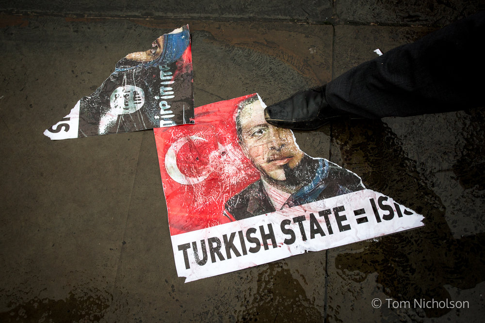 06/03/2016. London, UK. A man rubs his foot on a poster comparing Turkish president Recep Tayyip Erdoğan to ISIS, during the 'Break the Silence' demonstration against the Turkish government's treatment of Kurds.