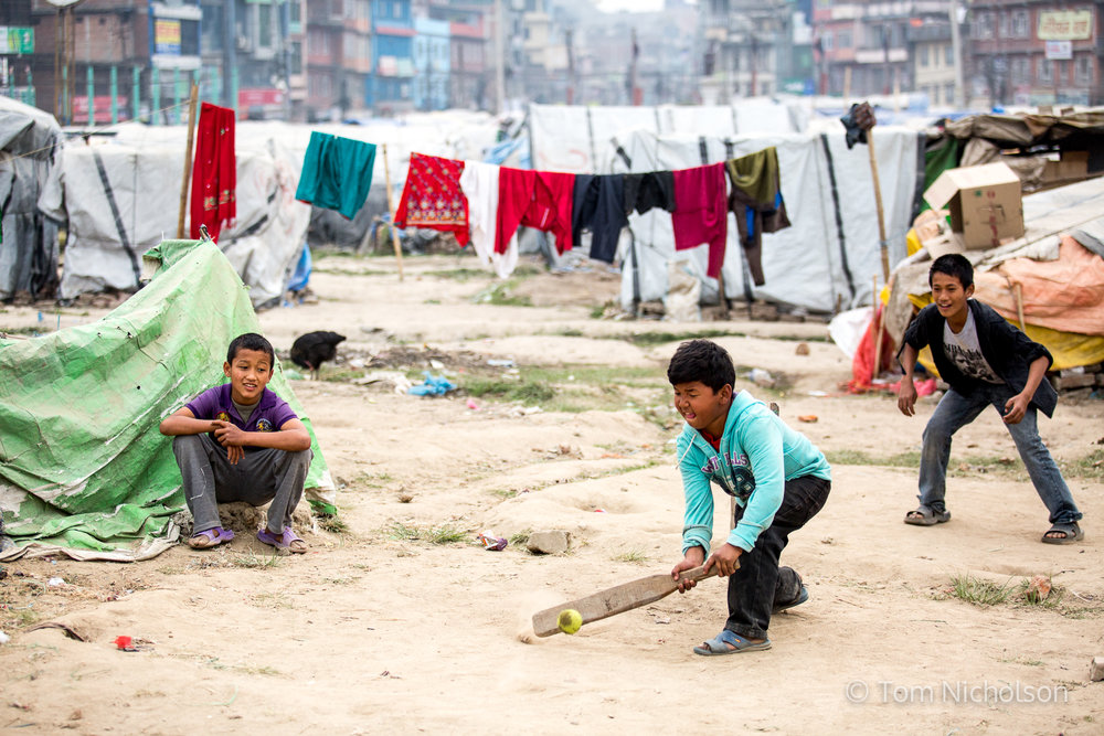 27/03/2016. Kathmandu, Nepal. Children play cricket in the Internally Displaced Person (IDP) camp in Chuchepati, Kathmandu City. The camp houses people in temporary accommodation following the April 2015 earthquake.