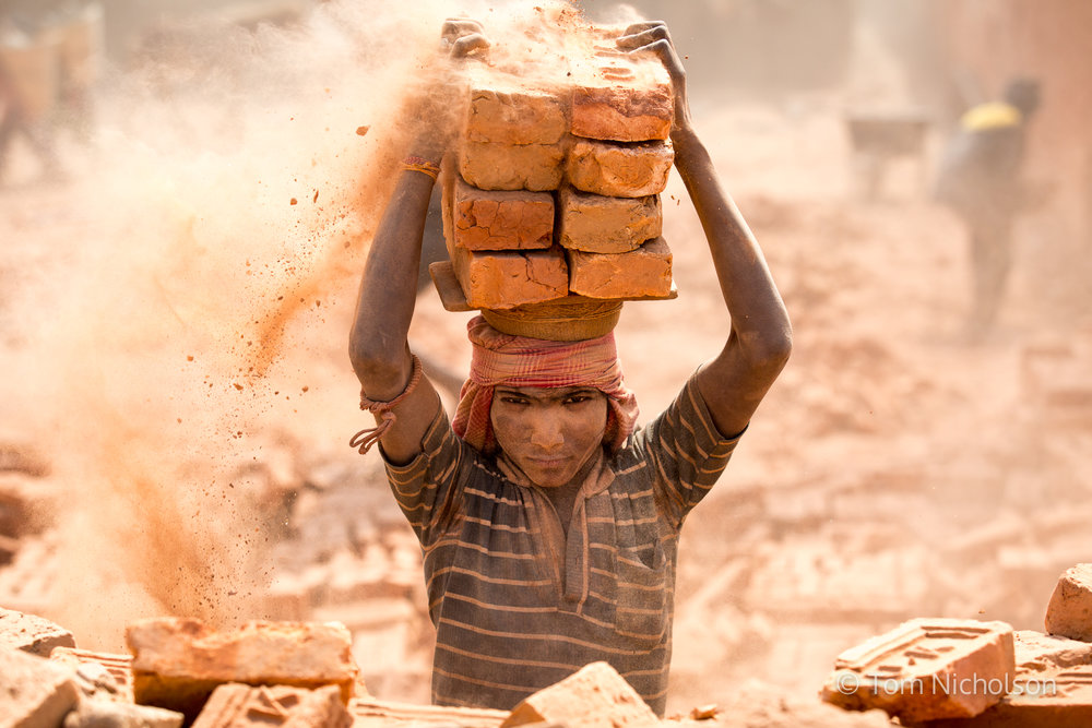 15/03/2016. Bungamati, Nepal. An Indian migrant worker carries bricks in the UK brickworks factory. Around 400 labourers, including children, work long hours for very little pay, in very dusty and hot conditions.