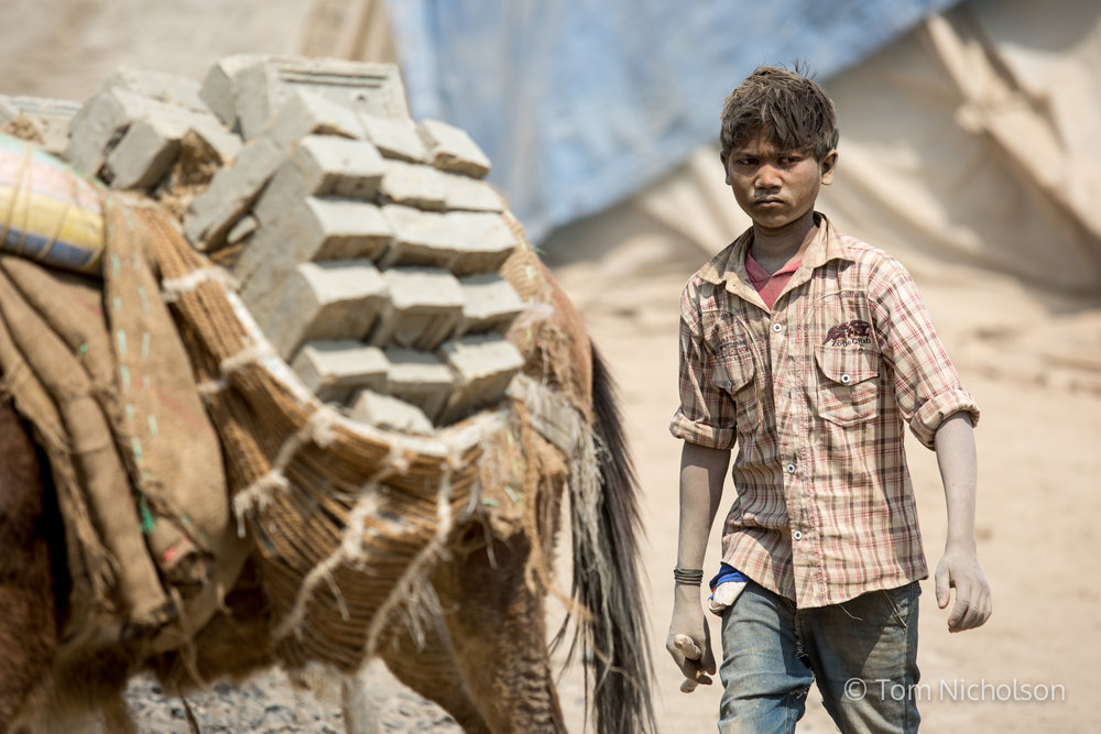 A child moves bricks in the UK brickworks factory in Bungamati, Kathmandu, Nepal on 15 March 2016. Around 400 labourers, including children, work in very dusty and hot conditions.