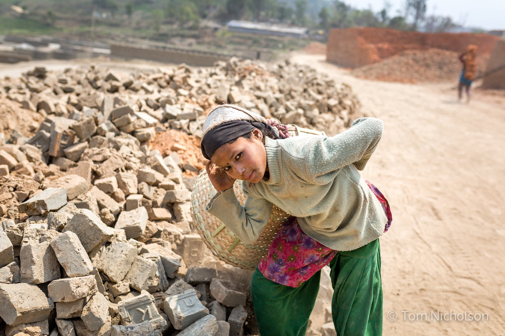 Children move bricks in the UK brickworks factory in Bungamati, Kathmandu, Nepal on 15 March 2016. Around 400 labourers, including children, work in very dusty and hot conditions.