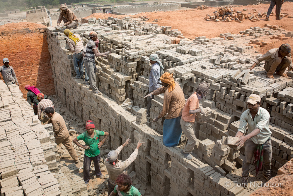 Labourers move bricks in the UK brickworks factory in Bungamati, Kathmandu, Nepal on 15 March 2016. Around 400 labourers, including children, work in very dusty and hot conditions.