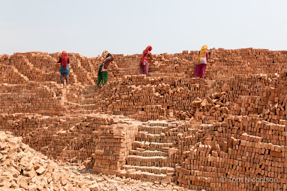 Women stack bricks in the UK brickworks factory in Bungamati, Kathmandu, Nepal on 15 March 2016. Around 400 labourers, including children, work in very dusty and hot conditions.