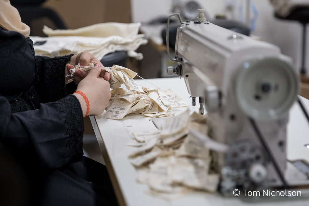 ©2018 Tom Nicholson. 23/06/2018. Irbid, Jordan. Asya, age 30, from Syria, is a seamstress working for Teenah, a social manufacturing company producing tote bags. The company provides support and work to vulnerable Syrian and Jordanian women who have often lost their husbands or the male breadwinner to the war, and therefore need an income to provide for their families. Asya lost 8 of her family members when their house was hit by a bomb during the war in Syria. Now thanks to Teenah, she has been able to afford to give her children a good education.