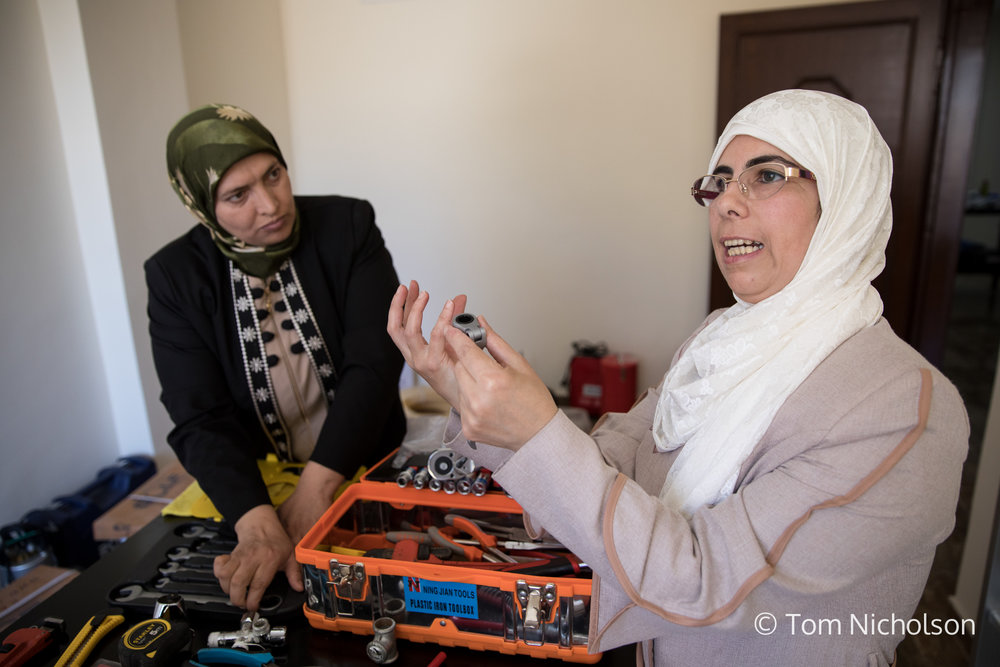 ©2018 Tom Nicholson. 23/06/2018. Irbid, Jordan. Safa, (right) is the owner of Safa Group, a company teaching and employing Syrian and Jordanian women how to become plumbers. Safa used to live in Syria, but she came back to Jordan in 2013 when the war started. She heard about a plumbing workshop & was interested in learning how to serve the needs of her own home. She quickly realised there was a market for female plumbers, as widowed women or those whose husbands were away, were more comfortable having a female plumber in the house. Friends and neighbours were critical at first, but soon became interested. Now Safa trains many female Jordanian and Syrian refugees to become plumbers, so they can earn a living or just fix their own sinks and toilets.