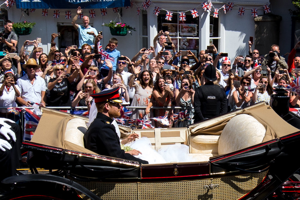 Crowds cheer and take photos of Prince Harry and Meghan Markle during the carriage procession after their wedding ceremony at St George's Chapel in Windsor Castle. May 2018 - Windsor, UK.