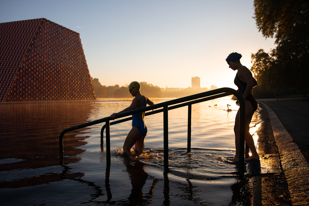 Swimmers enter the Serpentine Lido in Hyde Park at sunrise this morning. The temperature in the capital is set to reach 22 degrees Celsius later today. September 2018 - London, UK