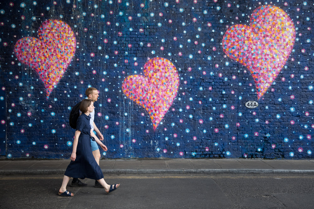 A man and woman walk past a heart mural near Borough Market, on the anniversary of the London Bridge and Borough Market terror attack. A series of events are taking place throughout the day, including a service of commemoration at Southwark Cathedral, the planting of an olive tree in the Cathedral grounds, a minute's silence at 4:30pm and the laying of flowers. June 2018 - London, UK.