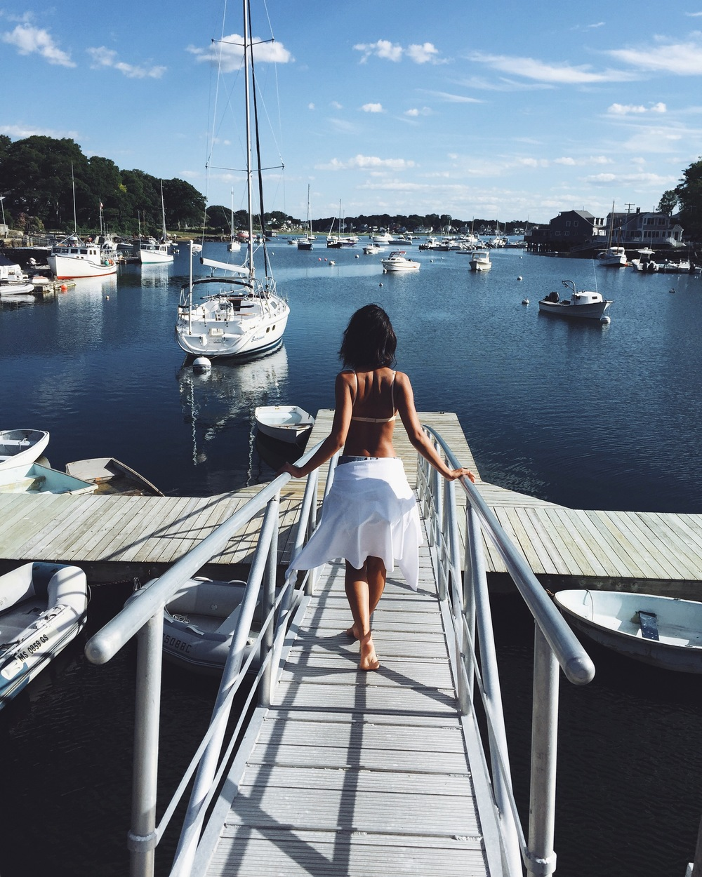 Blogger Claire Leana Millar of LatelyIveBeen.com wearing  Re/Done Shorts, Brandy Melville Nude Bralette, J. Crew White Button - Down on a sailing trip in New England