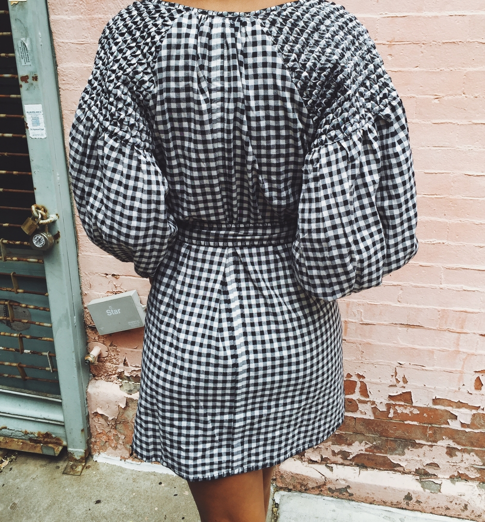Claire Leana Millar wearing an Innika Choo cotton black gingham dress & Givenchy rubber logo slides in Spanish Harlem