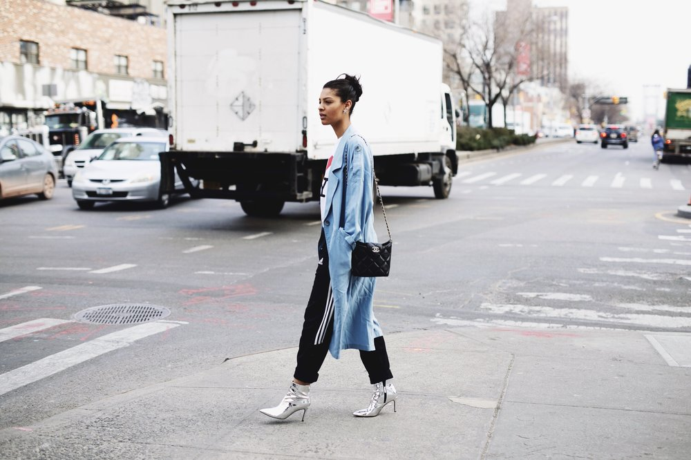 Claire Leana Millar wearing a TopShop Light blue Trench coat, Adidas track pants, TopShop Silver Boots, and an I love New York Tee Shirt