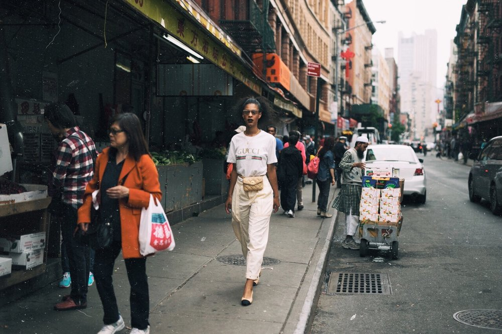 Claire Leana Millar in chinatown wearing a Gucci logo tee, tan Chanel fannypack,Chanel slingback pumps, Urban Outfitter parachute pants, + Adam Selman for Le Specs The Flex glasses