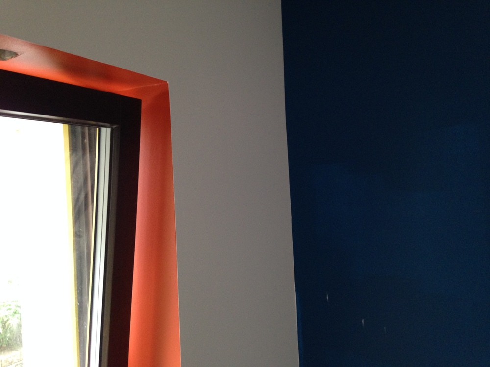 Window seat in the den with a pop of orange.  Blue wall will have white shelving/cabinets and the TV