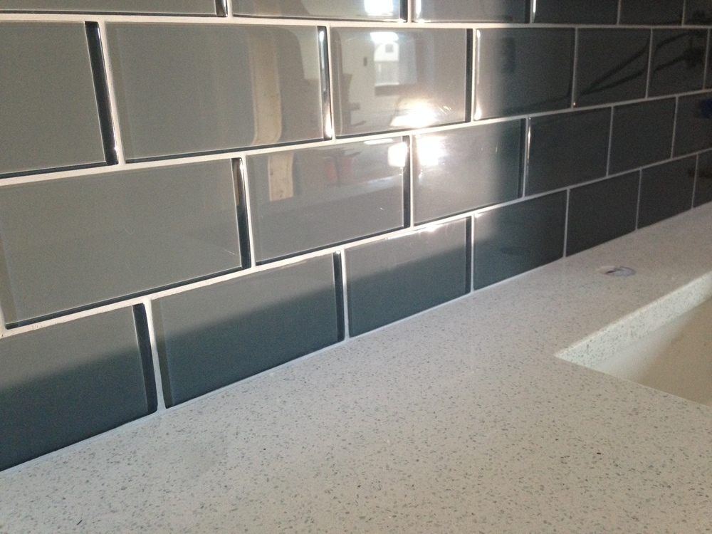 Master bath quartz counter top and glass wall tile