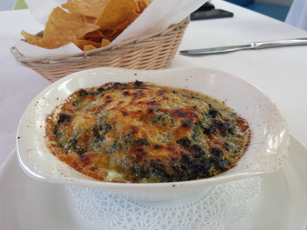 Spinach and artichoke dip topped with Gruyere.