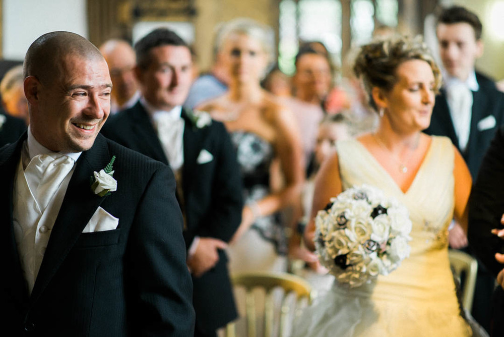 I think this might be a happy groom at The Bridesmaids get ready to walk down the Isle at Ordsall Hall Wedding Venue