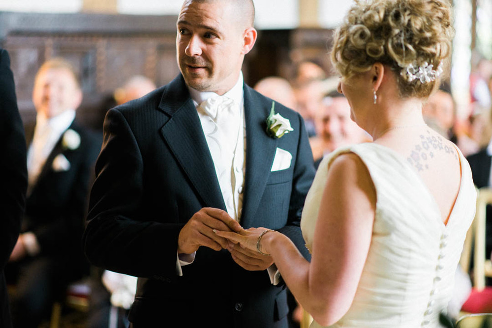 The Groom slides the ring onto the bride's finger Ordsall Hall Wedding Venue
