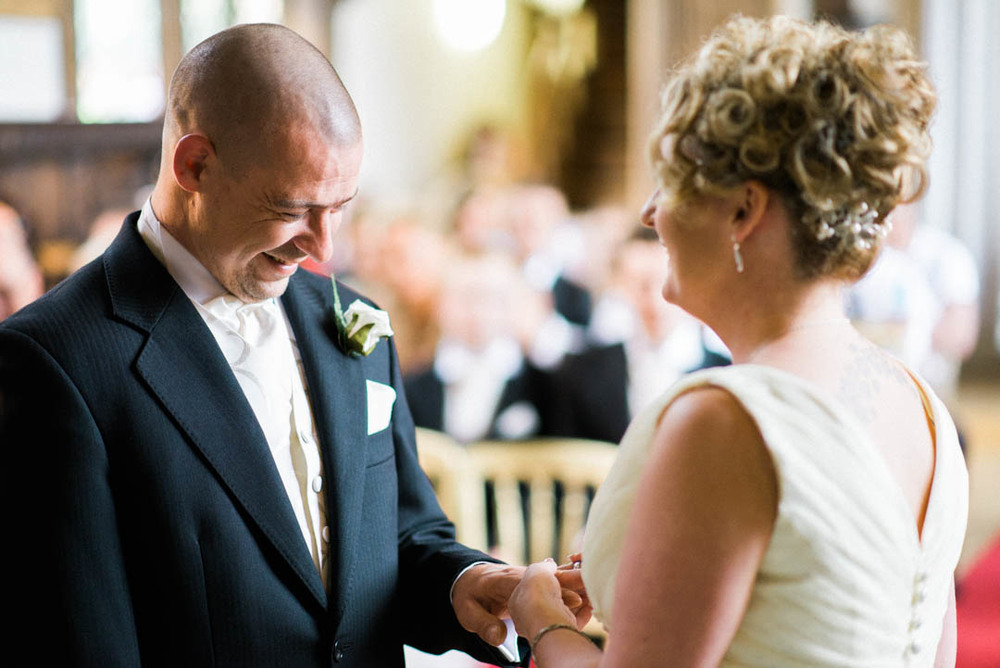 The Bride puts the grooms ring onto his finger at Ordsall Hall Wedding Venue
