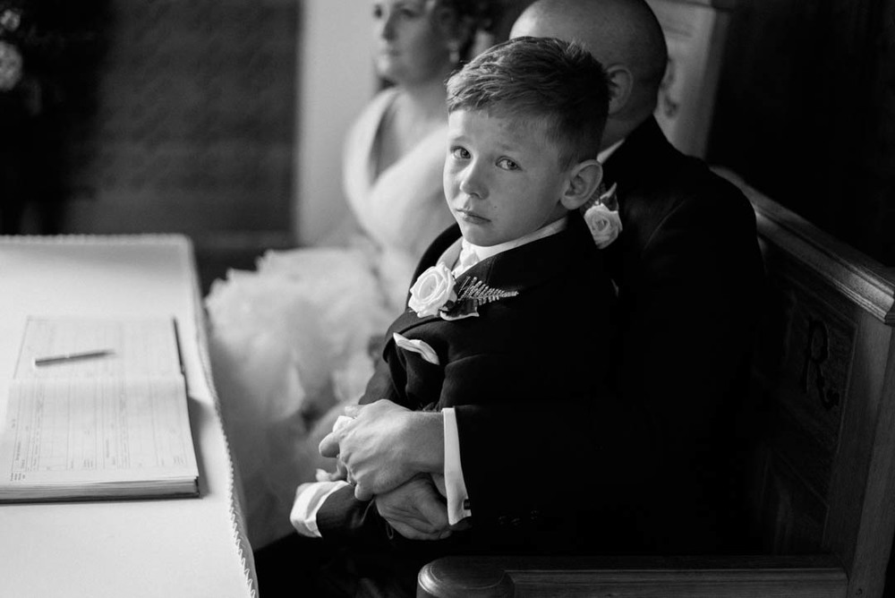 Pageboy cries with the bride and groom after the wedding at Ordsall Hall
